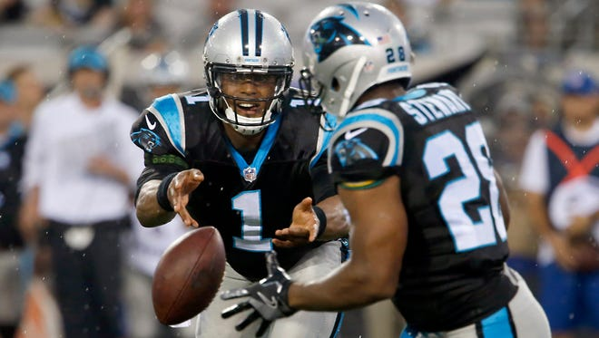 Carolina Panthers quarterback Cam Newton (1) tosses the ball to running back Jonathan Stewart (28) during the first quarter of an NFL football game at EverBank Field.
