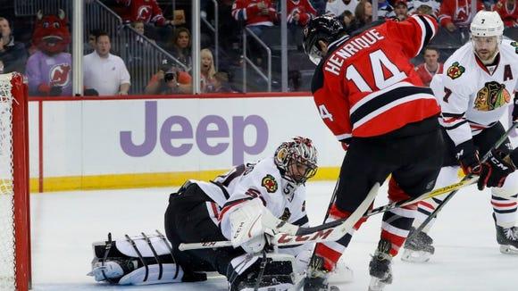 Blackhawks goalie Corey Crawford (50) blocks a shot attempt by New Jersey Devils center Adam Henrique (14) during the second period.