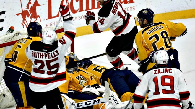 Devils center Adam Henrique, top center, celebrates after tying the score during the third period against the Nashville Predators on Thursday.
