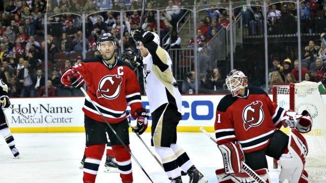 Penguins right wing Patric Hornqvist celebrates a goal by center Evgeni Malkin, not pictured, in front of Devils goalie Keith Kinkaid and defenseman Andy Greene during the first period Sunday.