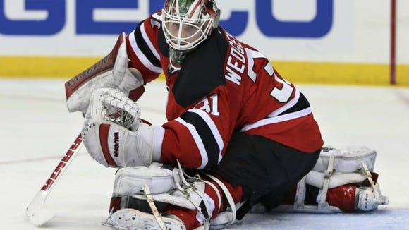 Devils goalie Scott Wedgewood (31) makes a glove-save during the first period.