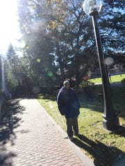 Patrick Norton stands near the spot where he says Sister M. Annella Zervas appeared to him as he was painting the light post Tuesday, Oct. 24, in St. Joseph.