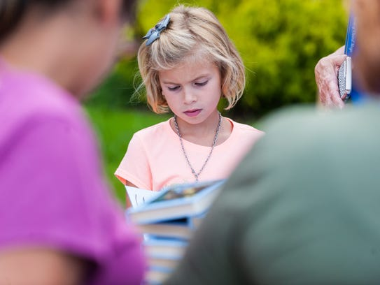 Cassidy Keller, 7, check out a stack of books during