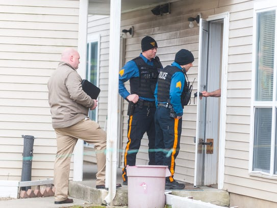Police talk to residents at they investigate a home-invasion robbery at the East Almond Estates in Vineland on March 15.