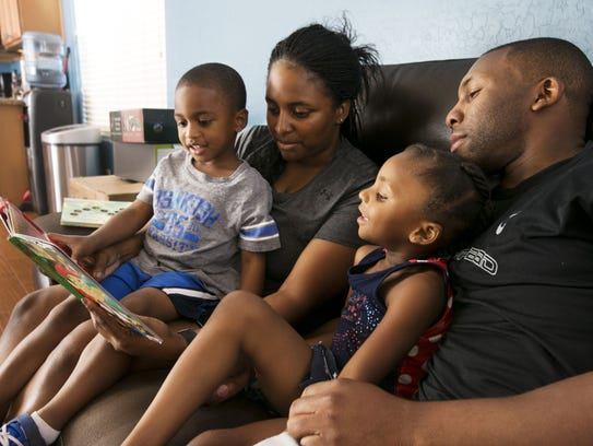 The Corley family reads a book at their home in Surprise.