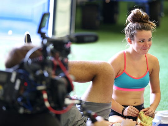 """As Blue Devils color guard member Catie Toal takes a break in rehearsal for the Drum Corps International competition on Thursday, Aug. 11, 2016, she is filmed for the Fuse television show  """"Clash of the Corps."""""""