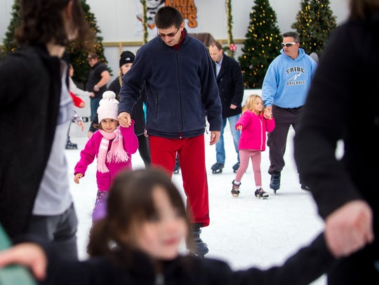 Parents hold their children's hands while skating at
