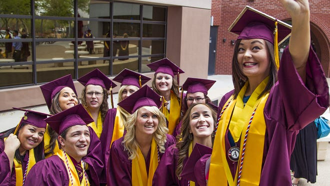 Arizona State University nursing students pose for a photo at the downtown campus before marching down 3rd Street to the Phoenix Convention Center for convocation, Tuesday, May 12, 2015. Victoria Tank holds the smartphone, right.
