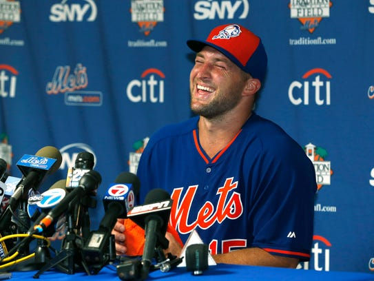 Tim Tebow laughs as he answers questions during a news