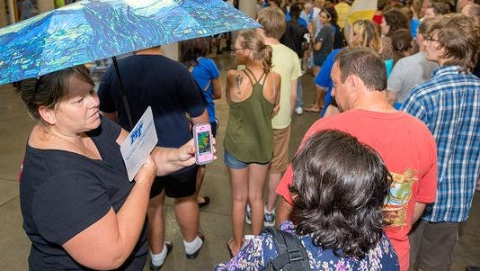 Tina Smith shows Lynne Skinner the local radar on her phone while in line for the President's Picnic on the concourse of MTSU's Floyd Stadium. (Photo: MTSU )