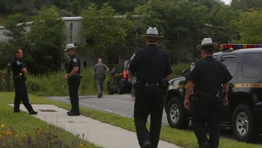 Putnam County sheriff's deputies and state troopers conduct an investigation near the scene of where a body was found behind an abandoned commercial building in Carmel.