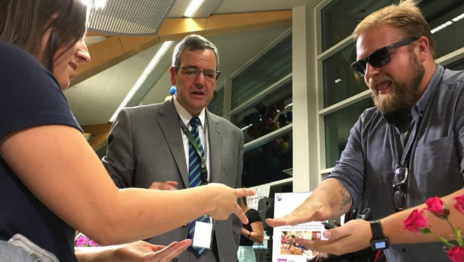 Champlain College President Donald Laakman, center, serves as one of the community judges for the Rock Paper Scissors Tournament that served as a fundraiser for ANEW Place on Wednesday, Sept. 21, 2016 at Burlington International Airport.