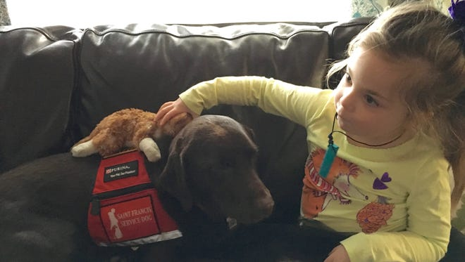 5-year-old Lucy Rhoden, who suffers from Dravet syndrome, plays with Hazel, a service dog trained to help Lucy.