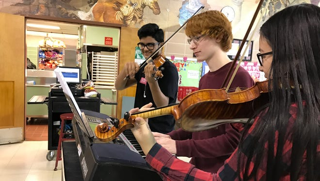 Washington Township High School chamber orchestra musicians (from left) Deven Patel, 16, on violin, James Gallicchio, 16, on piano and Andrea Eleazar, 16, serenade a classmate whose Valentine paid $5 toward a surprise song.