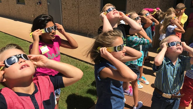 Second-grade students at Wylie Elementary School use special glasses to view the solar eclipse Aug. 21, the first day of school in the WISD.