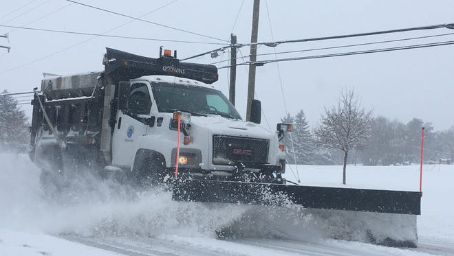 A snow plow clears North Coalter Street on Wednesday morning.
