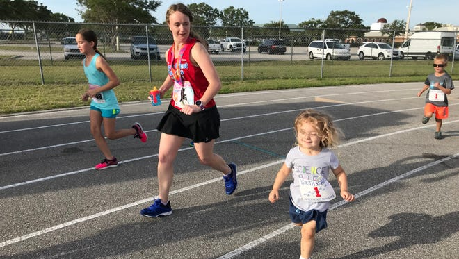 Isabella springs alongside her Mom during the kids race after the Viera Pizza 5K on Sunday.
