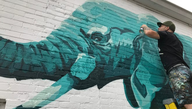 Cameron Moberg, a San Francisco-based artist, works Wednesday on a mural on the side of a building in the 300 block of Ferry Street in downtown Lafayette.