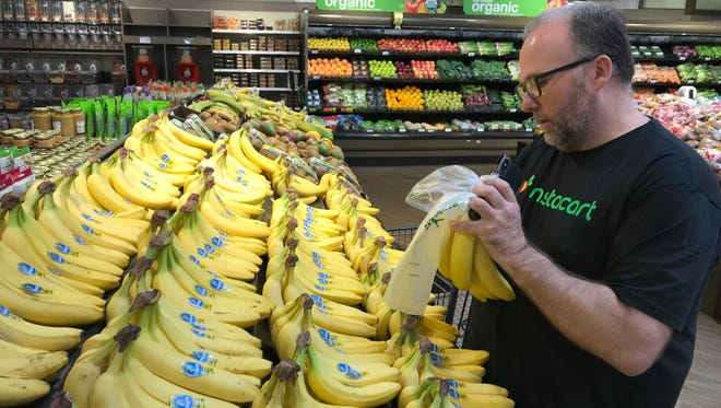 Instacart area manager Keith Janicke picks bananas at the Appleton Pick 'n Save.