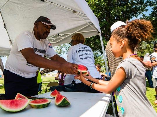 Organizer Ralph Powell hands a cool slice of watermelon
