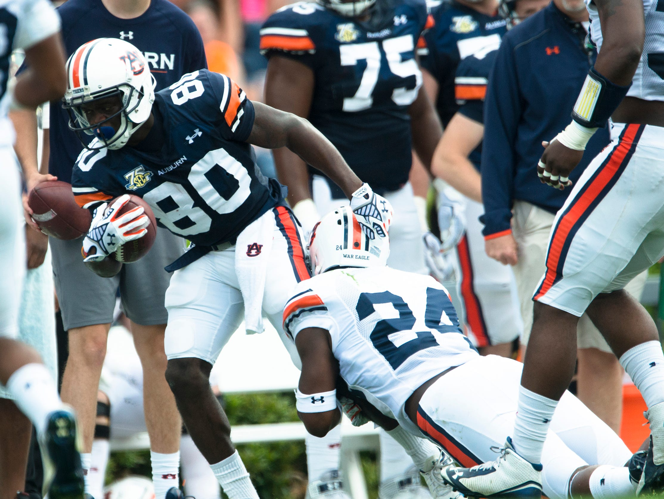 Auburn wide receiver Marcus Davis (80) is tackled by Auburn defensive back Derrick Moncrief during the Auburn A-Day spring game on Saturday, April 18, 2015, at Jordan-Hare Stadium in Auburn, Ala.