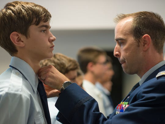 Maj. Dirk DeVille, the outgoing commander of Naples Cadet Squadron, pins a promotion pin on the uniform of Cadet Rhett Huter during a ceremony at the Naples Civil Air Patrol on Monday night, Aug. 22, 2016.