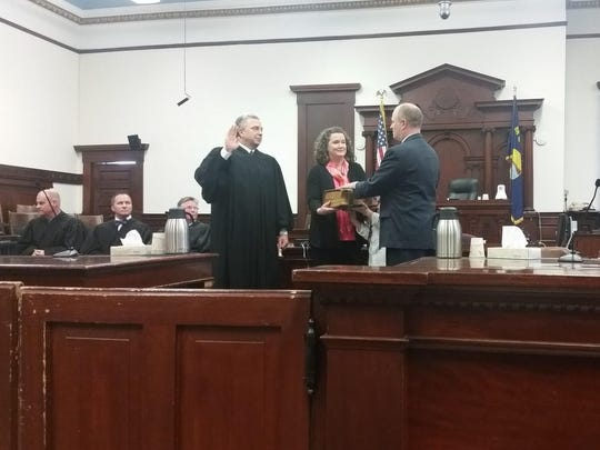 Montana Supreme Court Justice Dirk Sandefur swears in John Parker to the district judgeship at the Cascade County courthouse on March 31. Carrie, John's wife, holds the Parker family's bible.