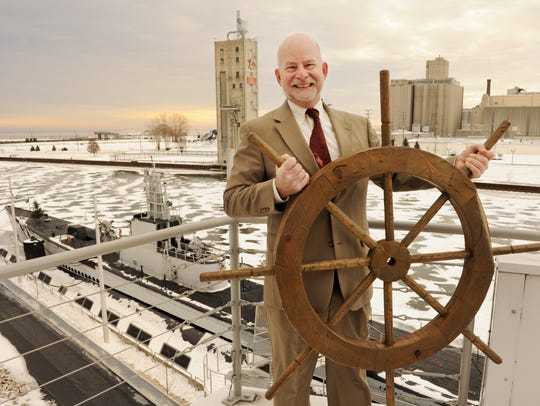 Rolf Johnson poses with a ship's wheel and the iconic