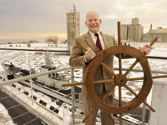 Rolf Johnson poses with a ship's wheel and the iconic USS Cobia Dec. 18, 2013, at the Wisconsin Maritime Museum shortly after being named the museum's CEO.