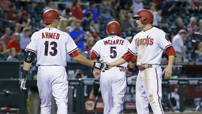 Arizona Diamondbacks shortstop Nick Ahmed (13) greets A.J. Pollock after they scored on a double by Paul Goldschmidt in the 8th against the Colorado Rockies in their MLB game Tuesday, April 28, 2015 in Phoenix, Ariz.