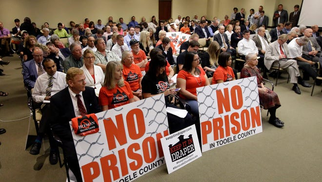 FILE - In this June 16, 2015, file photo, people watch during a public meeting with Utah lawmakers at the Utah State Capitol in Salt Lake City, about a plan to move the state prison. State officials have studied for years if and where they'll rebuild Utah's main state prison, and on Tuesday, Aug. 11, 2015, they're expected to finally pick a new location. (AP Photo/Rick Bowmer, File)