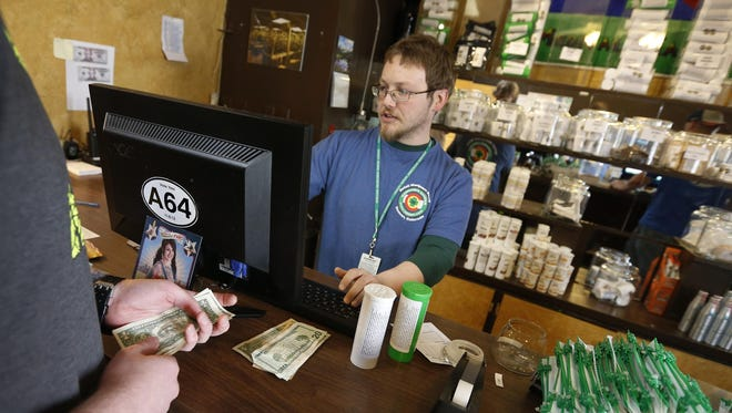 At a Denver retail store, a customer pays cash for marijuana. Legal marijuana remains an all-cash business because banks are wary about accepting money for an industry handling an federally controlled substance.