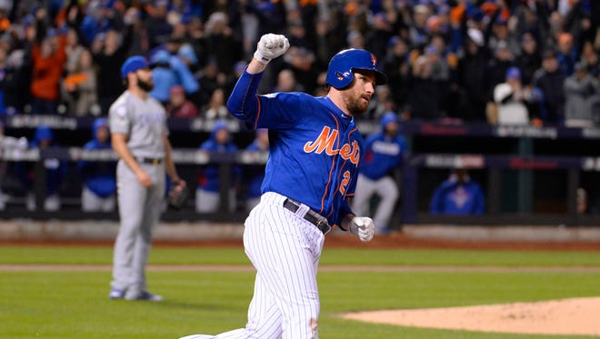 New York Mets second baseman Daniel Murphy (28) reacts after hitting a two-run home run against Chicago Cubs starting pitcher Jake Arrieta (background) in the first inning in game two of the NLCS at Citi Field.