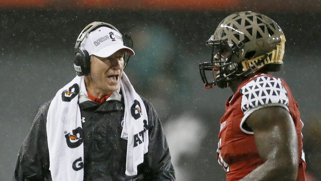 Bearcats head coach Tommy Tuberville shares feedback with defensive end Kimoni Fitz during an Oct. 24 Homecoming victory over UConn.