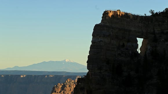 A viewpoint above Angels Window at the North Rim of the Grand Canyon offers views of the canyon below and Arizona's highest mountain, Humphreys Peak, beyond.