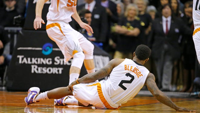 Phoenix Suns guard Eric Bledsoe (2) grabs his leg after falling to the floor in the first half of their NBA game against the Philadelphia 76ers Saturday, Dec. 26, 2015, in Phoenix.