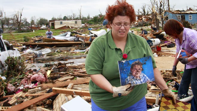 Tammy Niederhelman holds a photo of her son Zach Williams that she found May 24, 2011, while digging through rubble of her destroyed home in Joplin, Mo. Zach's body had not yet been found.