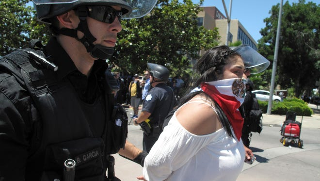 Police officers take a woman into custody after a Republican presidential candidate Donald Trump campaing rally in Fresno, Calif., on Friday, May 27, 2016. Police officers told hundreds of protesters to clear the streets in downtown Fresno following the Trump rally. Officers dressed in riot gear arrested two people on suspicion of unlawfully assembly after they refused orders.