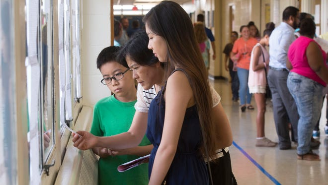 Ryan Zhang, left, and Queenie Zhang, right, look on as their mother, Sharon, center, locates her son's homeroom teacher's name during orientation for sixth graders at Ferry Pass Middle School Monday morning Aug. 8, 2016. Students in Escambia County return to school on Wednesday.