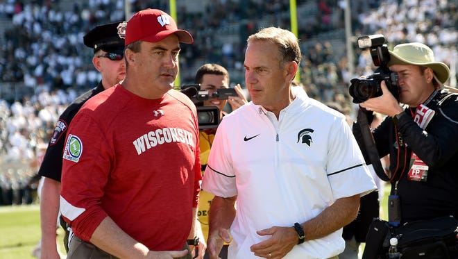 Paul Chryst, left, head coach of the Wisconsin Badgers, and Mark Dantonio, head coach of the Michigan State Spartans, meet after the game Sept. 24, 2016, in East Lansing.