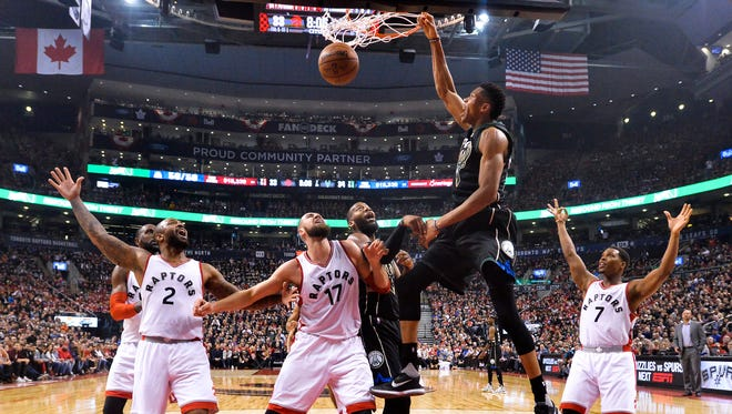 Bucks forward Giannis Antetokounmpo dunks over Raptors center Jonas Valanciunas in the first half Saturday in Toronto.