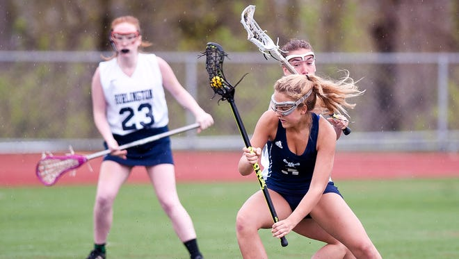 Mount Mansfield's Allison Charland (3) tries to shake free a Burlington defender during Tuesday's high school girls lacrosse game at Buck Hard Field.