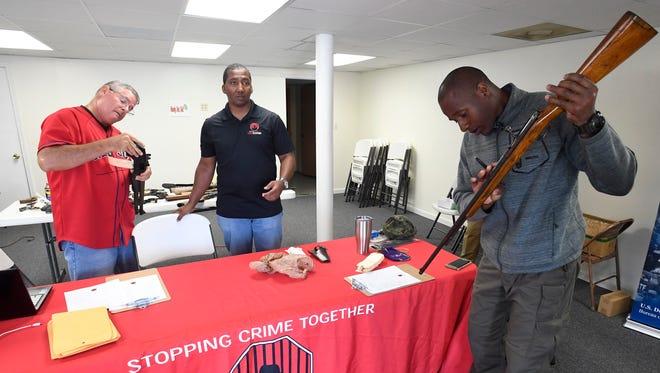 Tony Garrett, center, Sgt. M.W. Hoffman, left, and Officer Frederick Brewer, right, check guns at a CrimeStoppers gun buy back program in 2017.