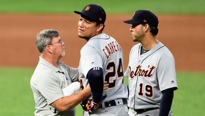 Tigers head trainer Kevin Rand and pitcher Anibal Sanchez check on first baseman Miguel Cabrera during the fourth inning of the Tigers' 6-3 win on Friday, July 21, 2017, in Minneapolis.