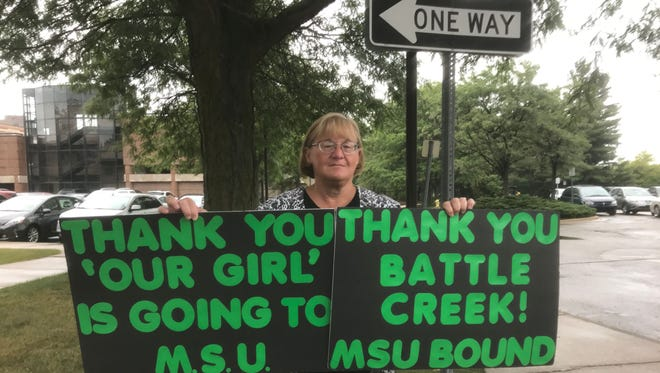Lori Truex of Battle Creek Mich., holds the signs she'll carry Aug. 30, 2017, to thank everyone for their donations to help her daughter, Kendall, attend Michigan State University in East Lansing, Mich.