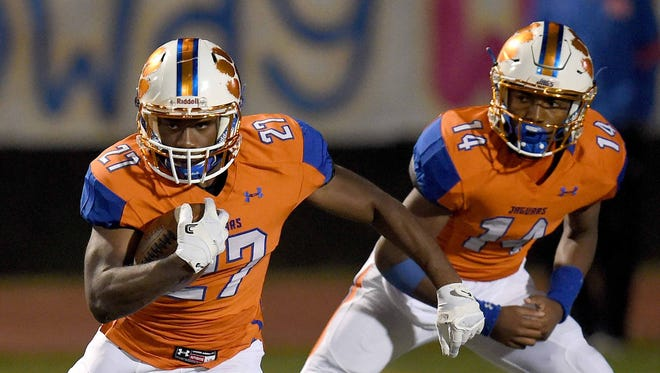 Madison Central's Cedric Beal (27) looks for running room after taking the handoff from quarterback Jimmy Holiday (14) during a MHSAA Class 6A first round playoff game on Friday, November 10, 2017, at Madison Central High School in Madison, Miss.