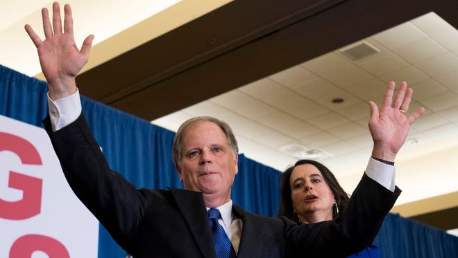 U.S. Sen.-elect Doug Jones and his wife, Louise, greet supporters as he claims victory at his watch party in Birmingham, Ala., on Tuesday.
