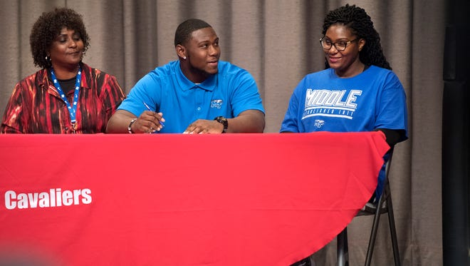 Crockett County's Jordan Branch smiles at coach Kevin Ward on Wednesday before signing his national letter of intent to play football at MTSU.