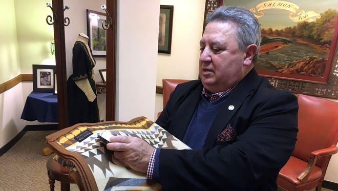 In this Feb. 15, 2017, photo, former Oregon Sen. Republican leader Ted Ferrioli examines a Pendleton blanket in the state Capitol that had been sent to him by the board of directors of Confederated Tribes of Umatilla. After asking the state ethics commission if he could accept the blanket, given in recognition of work Ferrioli had done on behalf of Indian tribes, and considering various options, he decided to present it for display in a room in the Capitol.