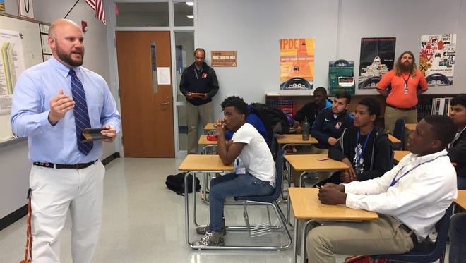 Will Owens, left, talks to the Carolina High football players Thursday after being introduced as the school's new football coach.